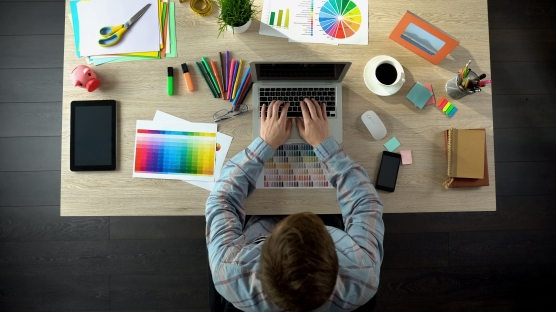 Creative designer typing on laptop, sending art project to client, top view